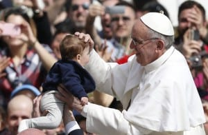 Pope Francis blesses child in St. Peter's Square after celebrating Palm Sunday Mass