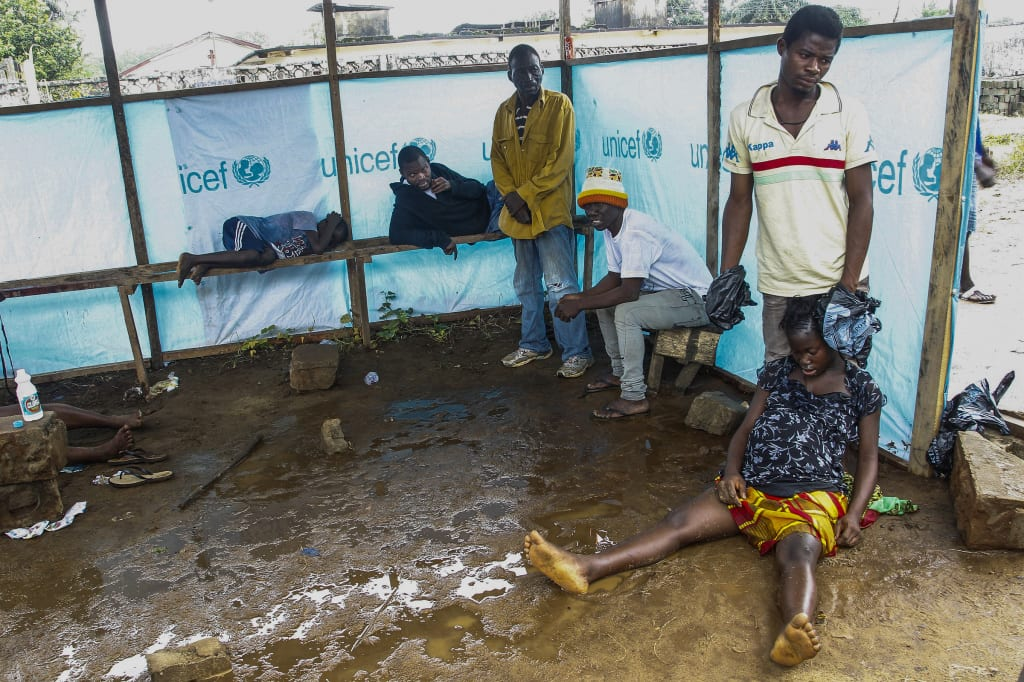 Liberians wait outside Ebola treatment center